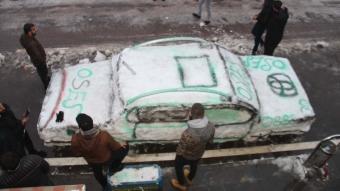 Yol kenarında biriken kardan araba yaptı