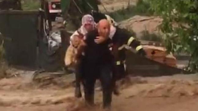Sel sularında köpeği ile mahsur kaldı, itfaiye eri sırtında taşıdı