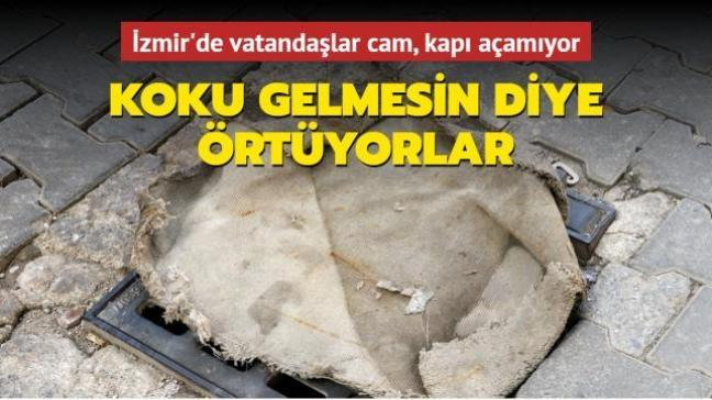 İzmir'de vatandaşlar kanalizasyondan koku gelmemesi için mazgalların üstünü örtüyor